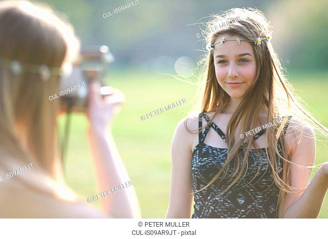 Teenage girl photographing best friend using instant camera in park