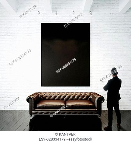 Man stands against holding blank white canvas and vintage classic sofa on the wood floor