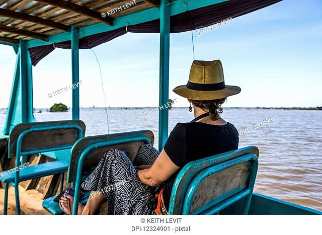A woman sits on a boat looking out at the water as it tours down a river; Siem Reap Province, Cambodia
