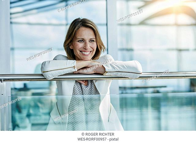 Happy businesswoman leaning on railing at the airport