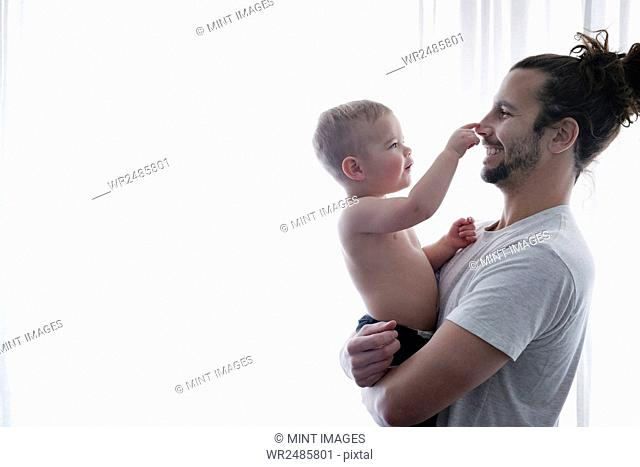 A young man holding a small child in his arms