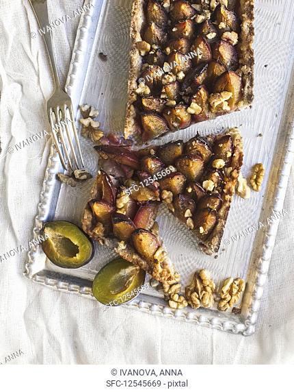Plum pie with walnuts on a silver tray over a white linen fabric surface