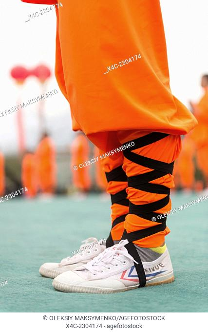 Shaolin Kung Fu student wearing Feiyue shoes and orange uniforml in DengFeng, Henan, China 2014