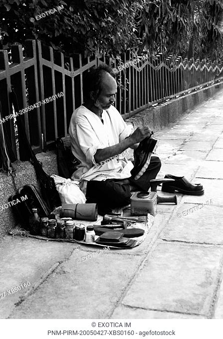 Shoemaker on footpath, New Delhi, India