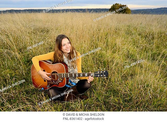 Smiling young woman playing guitar in field