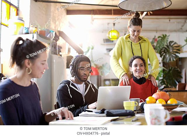 Young colleges student friends studying at kitchen table in apartment
