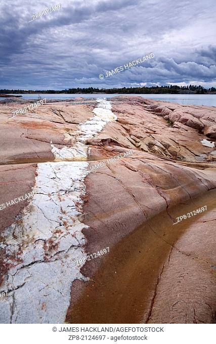 Incredible cloud formations and a White Quartzite strip running through Pink Granite along the shores of Georgian Bay in Killarney Provincial Park, Ontario