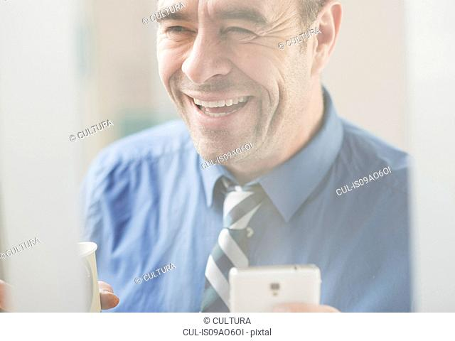 Mature businessman laughing in office