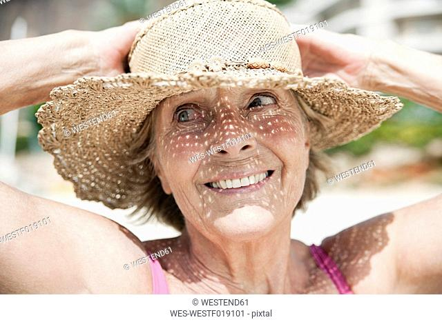 Spain, Senior woman with straw hat, smiling