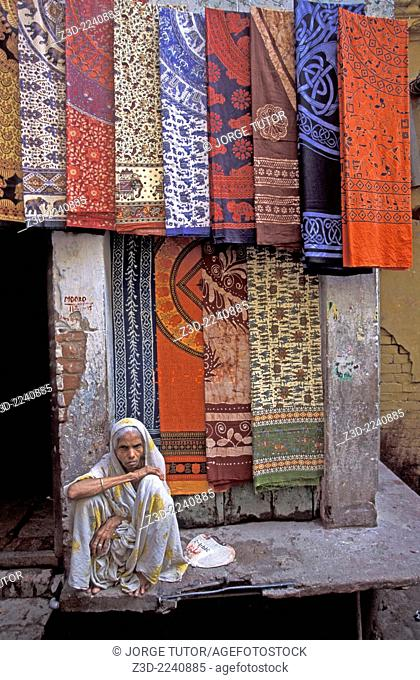 Terxtile old lady vendor in narrow old city alley Varanasi, Uttar Pradesh, India
