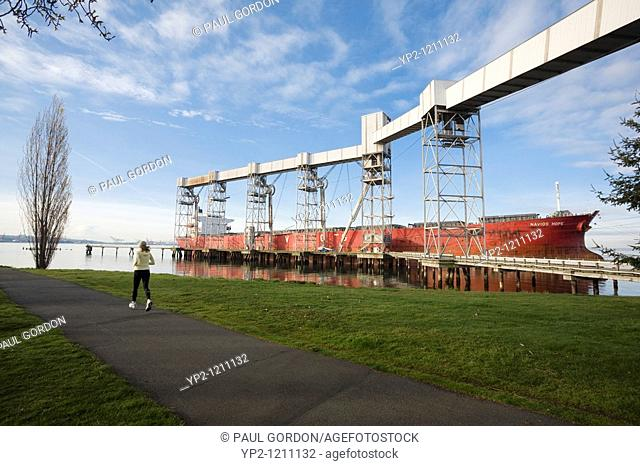 Woman Running at Myrtle Edwards Park, Cargo Ship Navios Hope Docked at the Port of Seattle Grain Facility in the Background, Seattle, Washington, Early Morning
