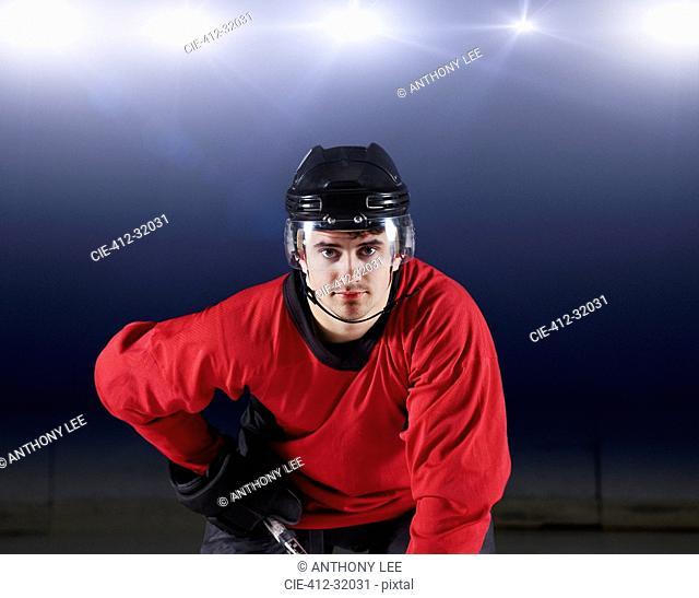 Portrait confident hockey player in red uniform