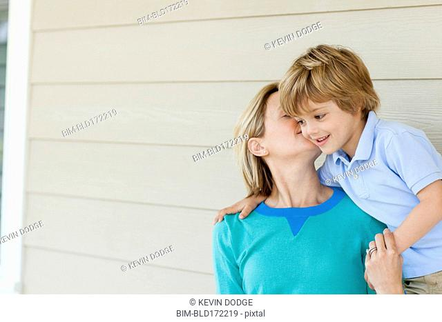 Caucasian mother kissing son on patio