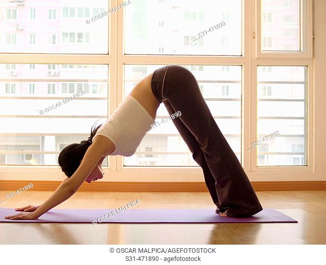 young asian girl practicing yoga at home