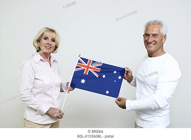 two mature people showing flag of Australia