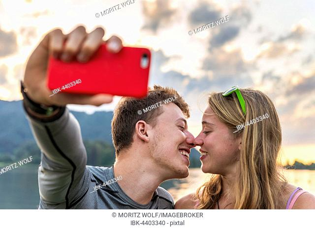 Young couple kissing, photographing themselves with mobile phone, selfie, Schliersee, Upper Bavaria, Bavaria, Germany