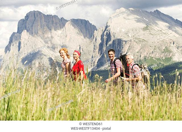 Italy, Seiseralm, Four persons hiking, side view, smiling, portrait