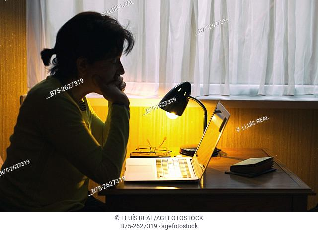 Silhouette of a young woman, working with a lap top on a table next to a window, with a lighted lamp