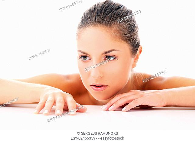 Portrait of a beautiful girl who is lying on her arms and posing over a white background