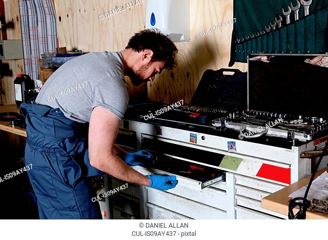 Male mechanic in workshop selecting wrench from his tool box
