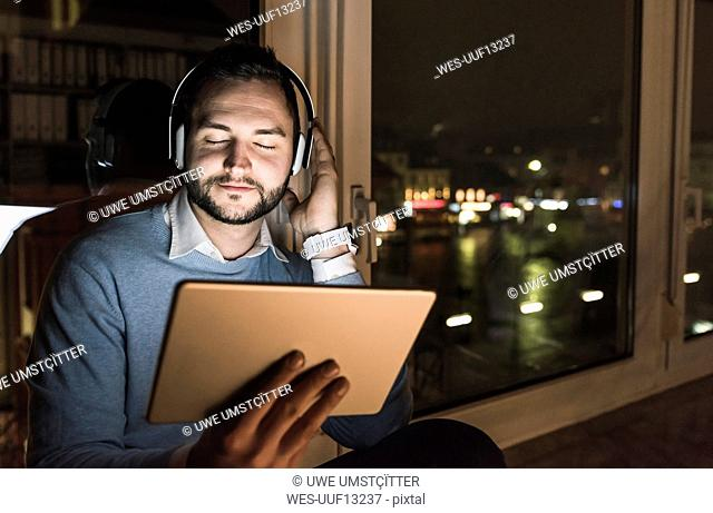 Businessman sitting on window sill in office at night listening music with headphones and tablet