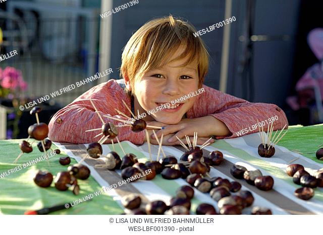 Portrait of happy little boy with tinkered chestnut figurines