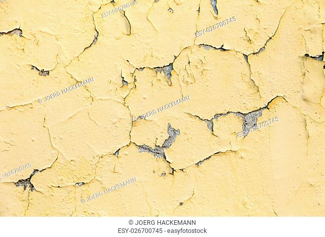 Background, peeling yellow and white paint on a rough surface