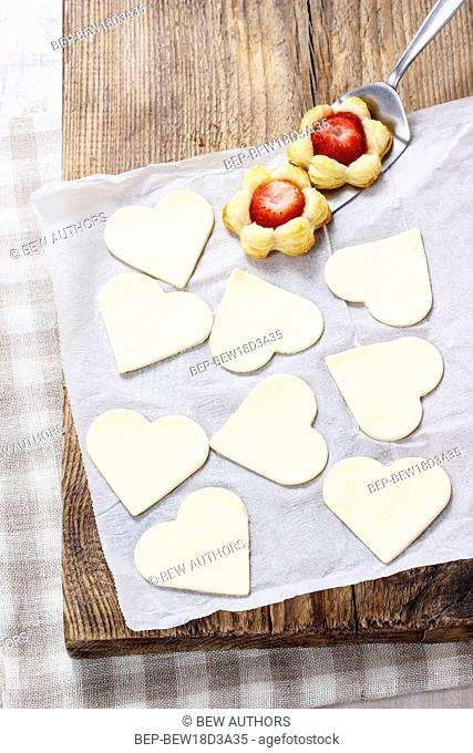 Making puff pastry cookies in heart shape filled with strawberries