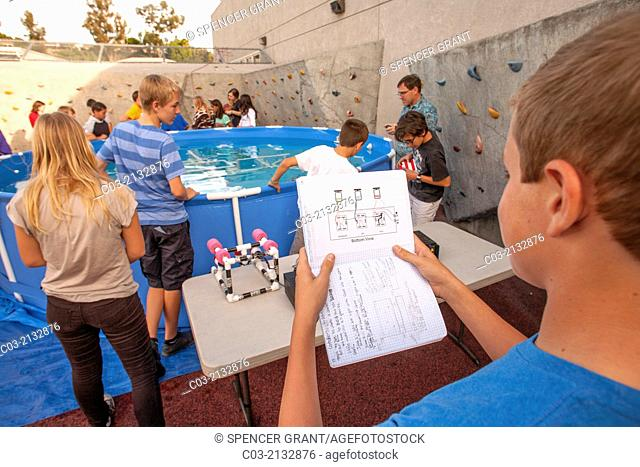 A middle school student in Mission Viejo, CA, refers to his notes as his classmates test the remote operated submarine vehicles (ROV) they built in their...