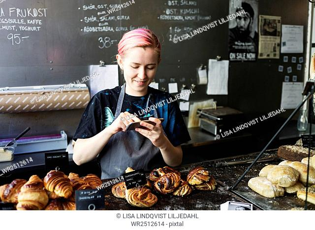 Smiling owner photographing breads in coffee shop