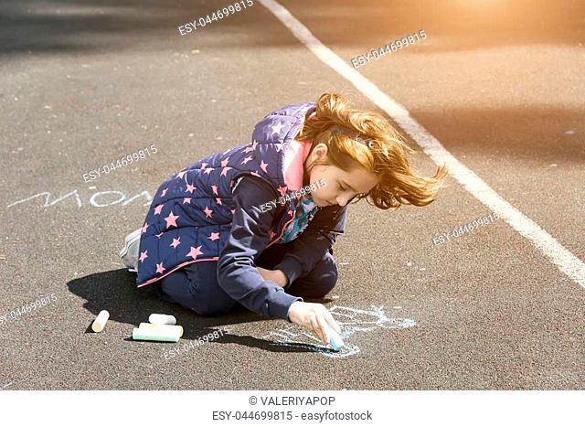 the child paints with chalk on the asphalt, a little girl in windy weather writes different inscriptions