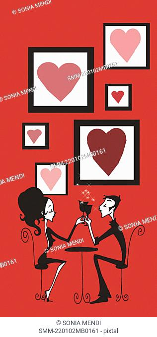 Couple toasting at cafe table in front of framed hearts