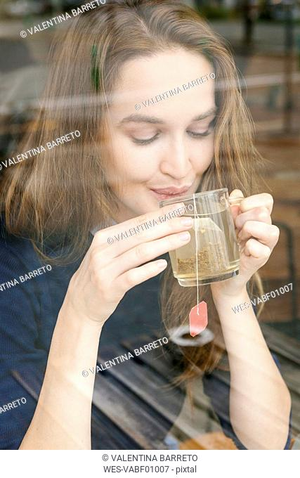 Smiling young woman drinking cup of tea in a cafe
