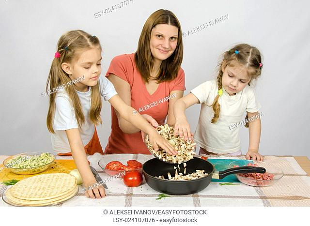 Two little girls at the kitchen table with a zeal to help her mother pour the mushrooms from the plate to the pan