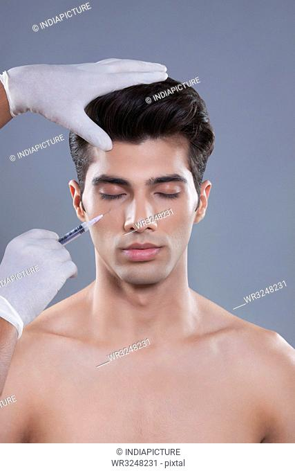 Young man getting botox injection