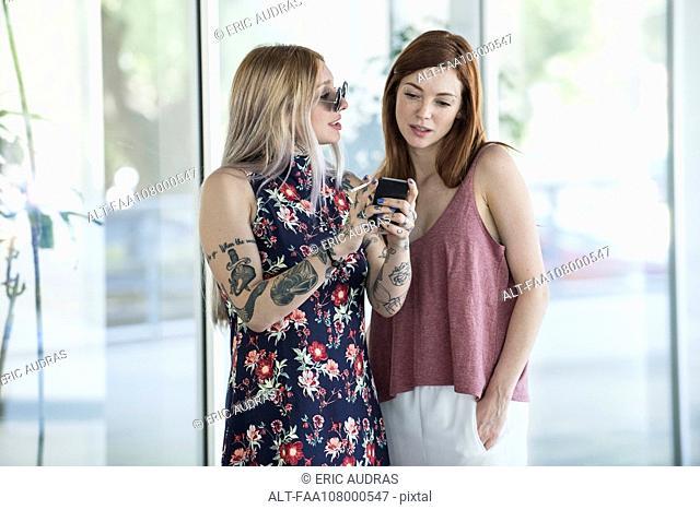 Women looking at smartphone while taking a smoke break