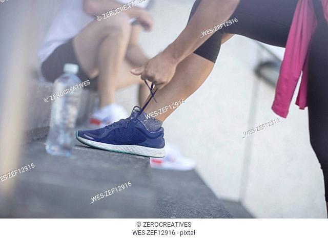 Legs of female athlete tying her sneakers