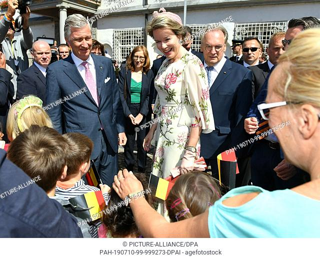 10 July 2019, Saxony-Anhalt, Wittenberg: The Belgian royal couple King Philippe and Queen Mathilde are greeted by onlookers and children with Belgian flags in...