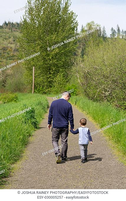 Father and son holding hands and walking down a path away from the camera in a realistic lifestyle portrait outdoors in Oregon