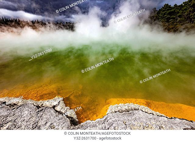 Champagne pool, burst of sunshine lights up foreshore during day of blowing mist and heavy rain, Wai-o-Tapu thermal region, Rotorua