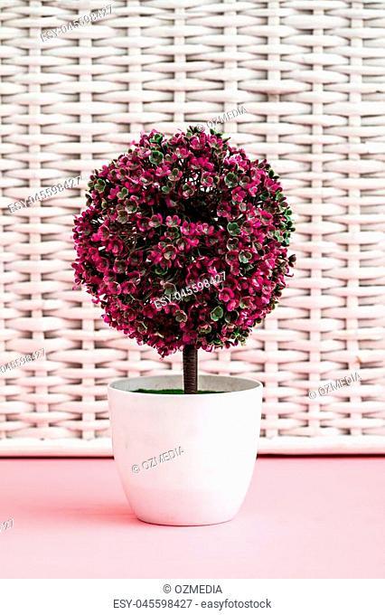 Artificial flower in white flowerpot on white background