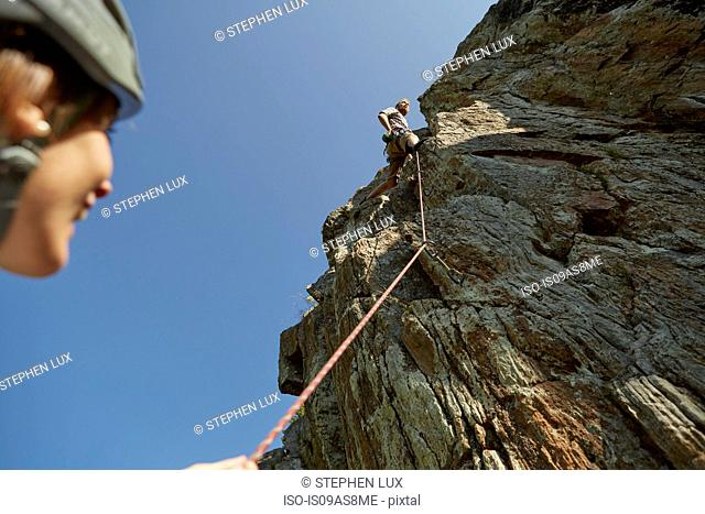 Low angle view of young rock climbing couple climbing rock formation, Val Senales, South Tyrol, Italy