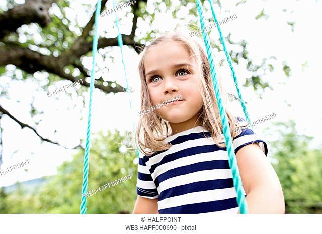 Portrait of little girl on a swing