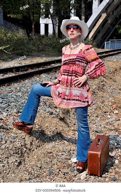 Boho style woman wearing white hat and sunglasses, standing next to a railway track under a bridge arch, with an old vintage suitcase on crushed stones