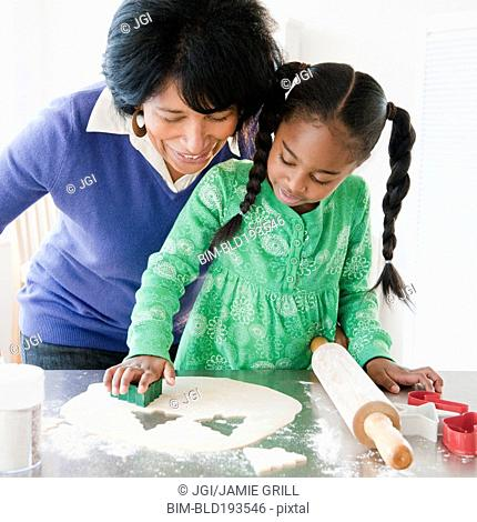 Black grandmother baking cookies with granddaughter