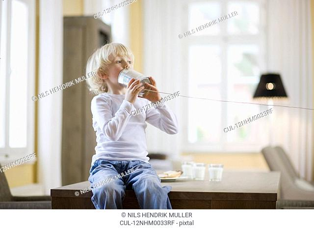 young boy playing with can phone