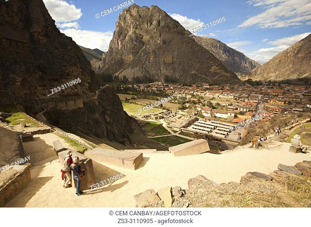 Guides with tourists at Ollantaytambo Archaeological Site looking at Pinkuylluna Incan Storehouses, Cusco Region, Urubamba Valley, Peru, South America