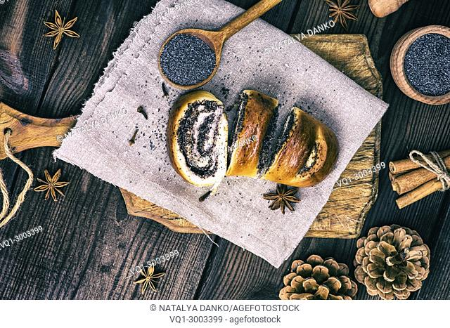 homemade roll with poppy seeds on a brown wooden board, top view, vintage toning