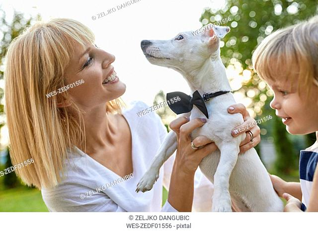 Happy woman with daughter holding dog wearing a bowtie outdoors