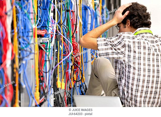 Frustrated technician working in Server room of data center